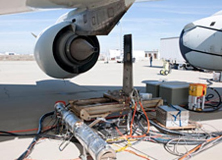 1-An emissions detection rake device is positioned behind the No.3 engine on NASA's DC-8 flying laboratory during ground tests of an alternative jet fuel made from chicken and beef tallow. (NASA / Tom Tschida)